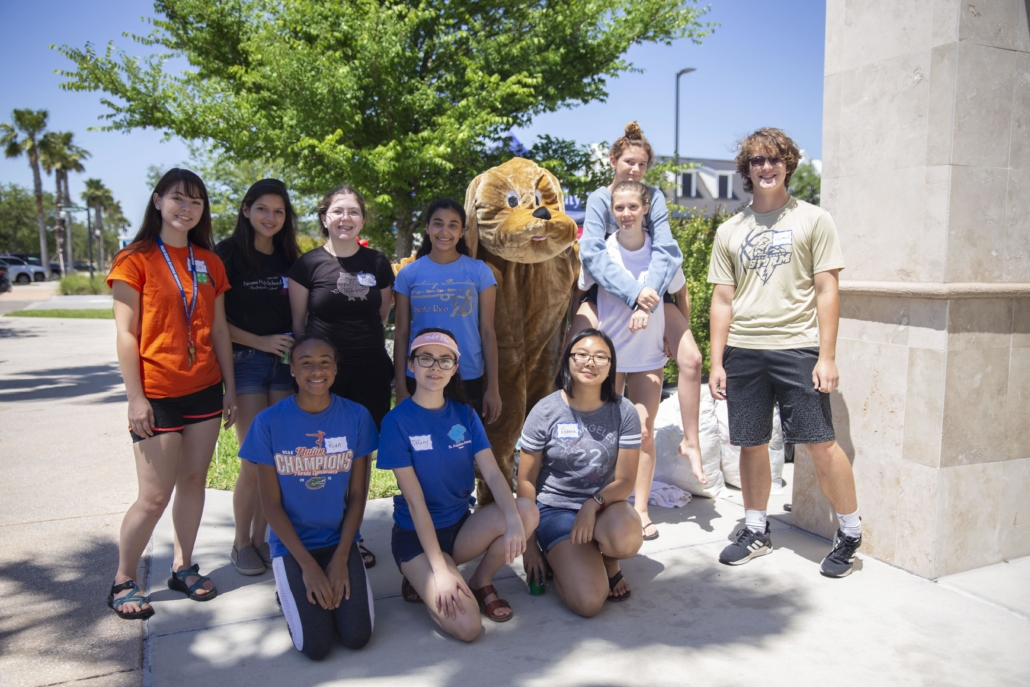 People posing for picture with animal mascot