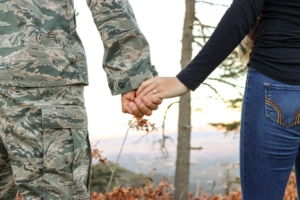 Military personnel holding wife's hand