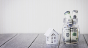 Close-Up Of Model House By Currency Jar On Table Against White Background